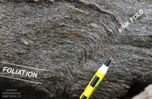 An outcrop of rock showing a grainy texture (former sandstone) that has been modified to develop a pronounced foliation. The trace of the foliation runs from the upper left to the lower right, and is deflected partway across the oucrop into a kink band (a crisp fold) that runs from lower left to upper right. As the foliation crosses the kink band from left to right, it dips down (gets steeper) before resuming its original orientation on the other side.