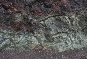 A photograph of a seaside outcrop, about 1 m tall by 1.5 m wide. In the middle, on the sand, a pencil serves as a sense of scale. The outcrop shows round forms (pillows) of green meta-basalt about 30 centimeters to 70 cm wide. The pillows are shown cross-section, showing a radial pattern of fracturess.