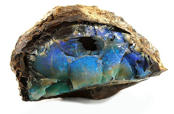 The mineraloid opal filling a void space in a rock sample from Australia. Mineraloids are not actual minerals because they do not contain an orderly and repeating crystalline structure. By Rob Lavinsky, iRocks.com is licensed under CC-BY-SA-3.0