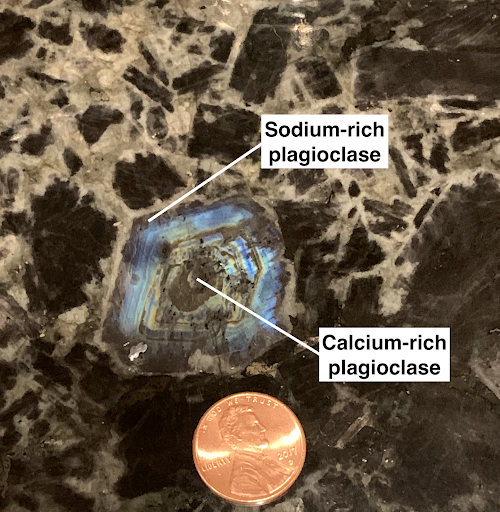 """""""Zoning"""" in a large crystal of plagioclase formed during the slow cooling of magma in an intrusive igneous body. The most calcium-rich concentration is located in the center that formed during the early cooling stages. The plagioclase became progressively more sodium-rich as cooling and crystal growth continued. The blue coloration is called """"schillerization"""" due to microscopic inclusions common to this variety of plagioclase. Photo by Shelley Jaye."""