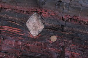 Photo of an outcrop of rock showing a dropstone of quartzite in banded iron formation.