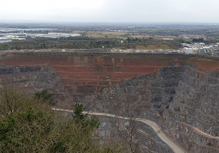 Photograph looking down into a quarry with gray rock on both sides and a big triangular wedge of red rock in the middle.