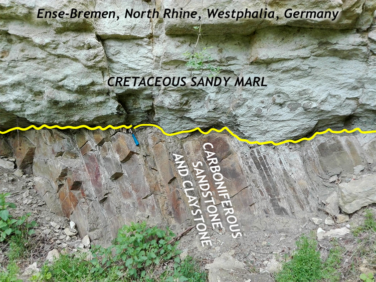Photograph showing horizontal granular massive layers overlying thin, right-dipping block layers. A hammer provides a sense of scale. Annotated copy.