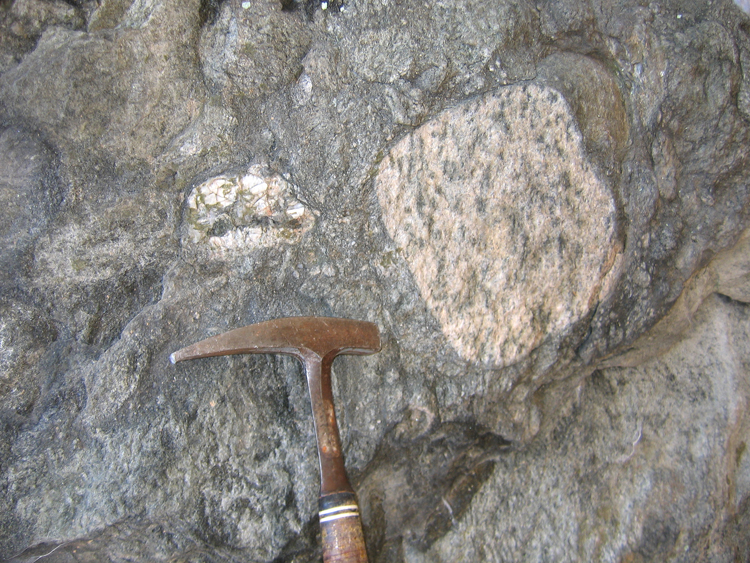 Photograph showing several outsized granite clasts in metadiamictite. A rock hammer provides a sense of scale.