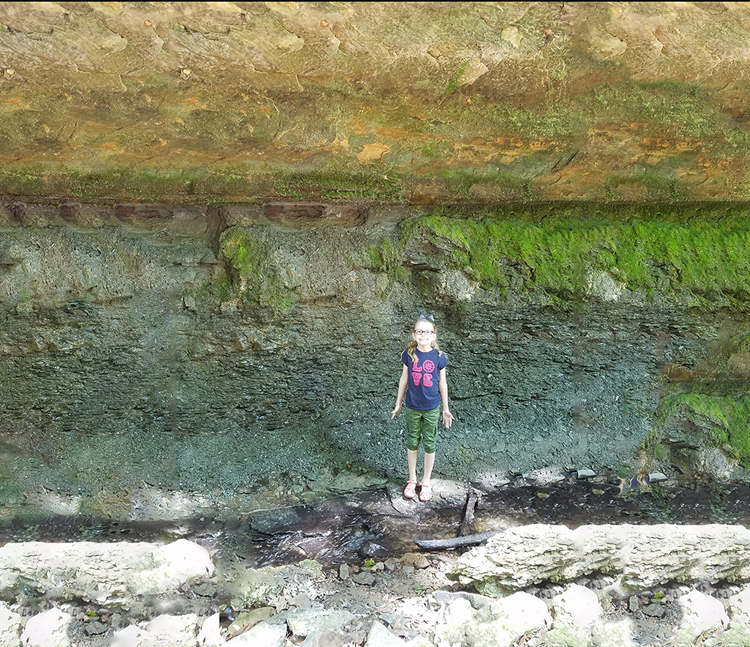 Photograph showing a disconformity, with horizontal sandstone lying on top of horizontal limestone+siltstone. A small girl provides a sense of scale; the outcrop cliff is about 4 meters high.