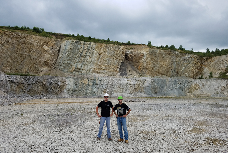Photograph showing a quarry, where steeply-dipping, faulted, and folded limestone layers terminate abruptly underneath a thin overlying layer of till. Two men serve as a sense of scale; the quarry wall is about 50 feet tall.