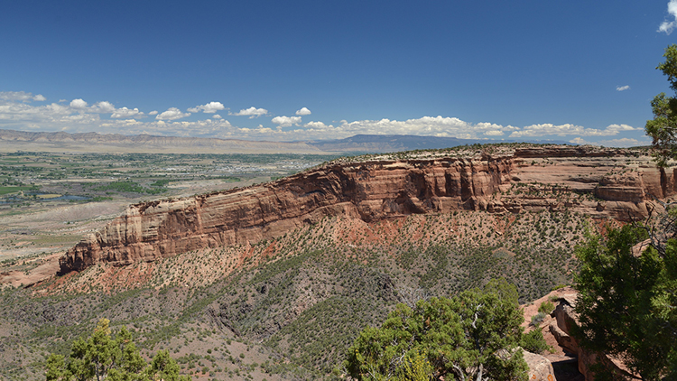 A photograph of a landscape in Colorado: a big cliff changes the angle of its strata from horizontal to slightly tilted at the left. Below the cliff is a layer of orange/tan shale, and below that a purple unit.