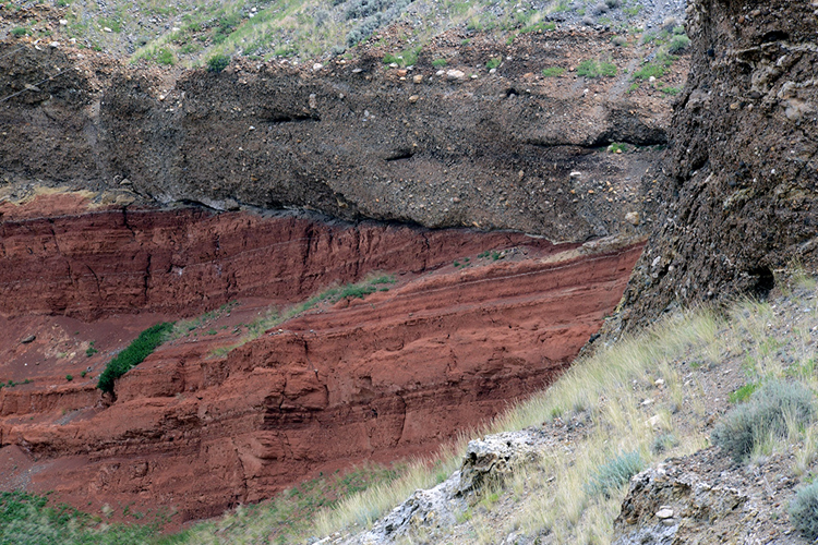Photograph showing a cliff-like exposure of horizontal gray gravel on top of bright red/orange thin sandstone layers that dip to the left.