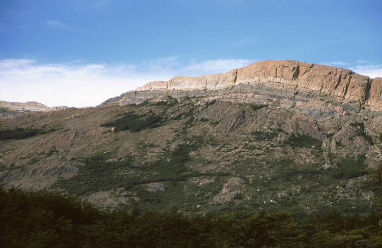 Landscape photo of a region in Argentina, showing low-lying hills with vertical bedding, and they are topped by big cliffs of volcanic layers.