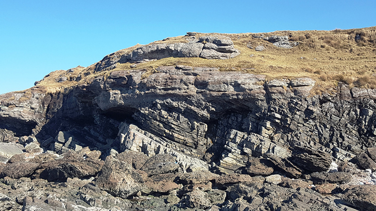 Photograph showing a Scottish seaside cliff outcrop, with thin right-dipping layers below, and horizontal, thick layers above.