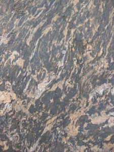 Photograph of a ~1m by 2m outcrop of migmatite, showing wispy blobs of pinkish granite amid a stretched-out dark matrix. A quarter (coin) serves as a sense of scale.