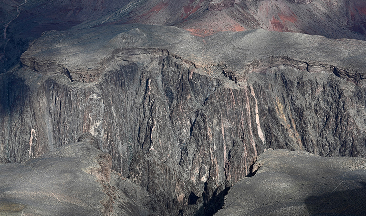Photograph of a cliff in the Grand Canyon, with horizontal layers of sandstone overlying a massive, craggy slope of metamorphic and plutonic rocks.