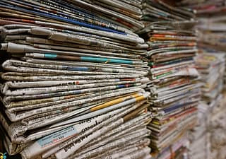 A photograph of a several stacks of newspapers, viewed from the side.