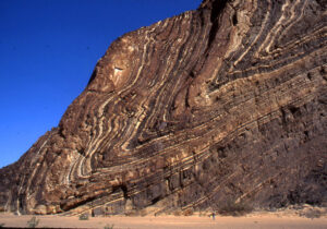 Photograph showing a cliffside outcrop in the desert. Rock layers dip moderately to the left, then make an abrupt turn, and head up again, with an even steeper dip: The upper limb of this synclinal fold is overturned.