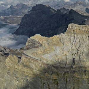 Aerial photo of raw, rocky mountains, showing folded rock layers that lie on their side, making a >>>> shape.