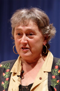 Photograph of biologist Lynn Margulis. She has gray hair, gold hoop earrings, and a blazer embroidered with leaves and flowers.
