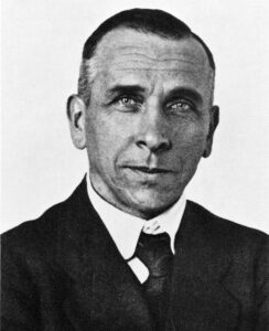 Old photograph of a young Alfred Wegener. He is clean shaven, with slicked-back hair, and a suit and tie.