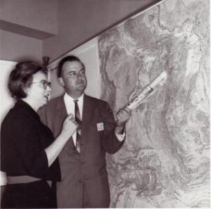 Old photo of Bruce Heezen and Marie Tharp in front of a wall-sized reproduction of their map. Tharp is wearing a dress and glasses. Heezen is in a suit; he gestures toward the Mid-Atlantic Ridge on the map with a rolled up newspaper.
