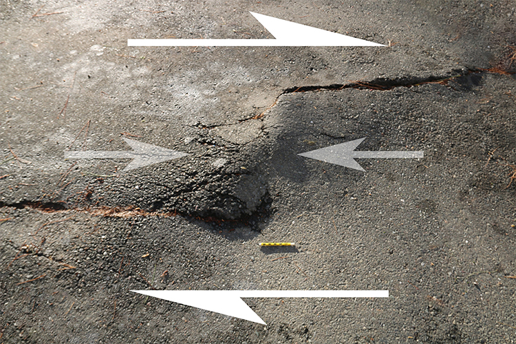 Annotated photograph of a 3m x 2m area of parking lot pavement. There are two cracks in the pavement: one coming in at the left edge of the frame, about 2/5ths of the way up from the bottom of the photo to the top, and dying out midway across the photo. A second crack starts at the right side of the photo, about 1/5th of the way down from top to bottom, and comes across to the mid-point. Between them is a bulge that is popping upward due to compression. A pencil provides a sense of scale.