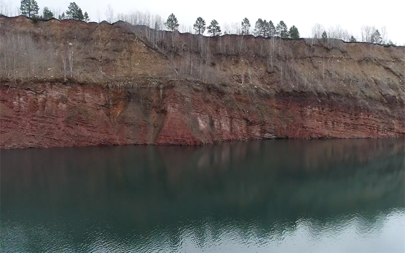 Photograph of a cliff next to a lake. The lower half of the cliff is a steep wall of red rock layers, gently dipping off to the right. Above that is a grayish zone that has more trees and appears to weather more easily.