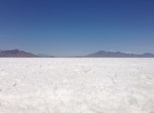 Photo of salt crust at the Bonneville Salt Flats in Utah with mountains in the background.