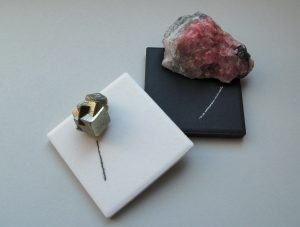 Pyrite showing a black streak on a white streak plate and rhodochrosite with a white streak on a black streak plate