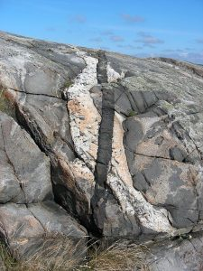 Photo of rock outcrop with a dike cutting through an older rock and another dike cutting across that one.