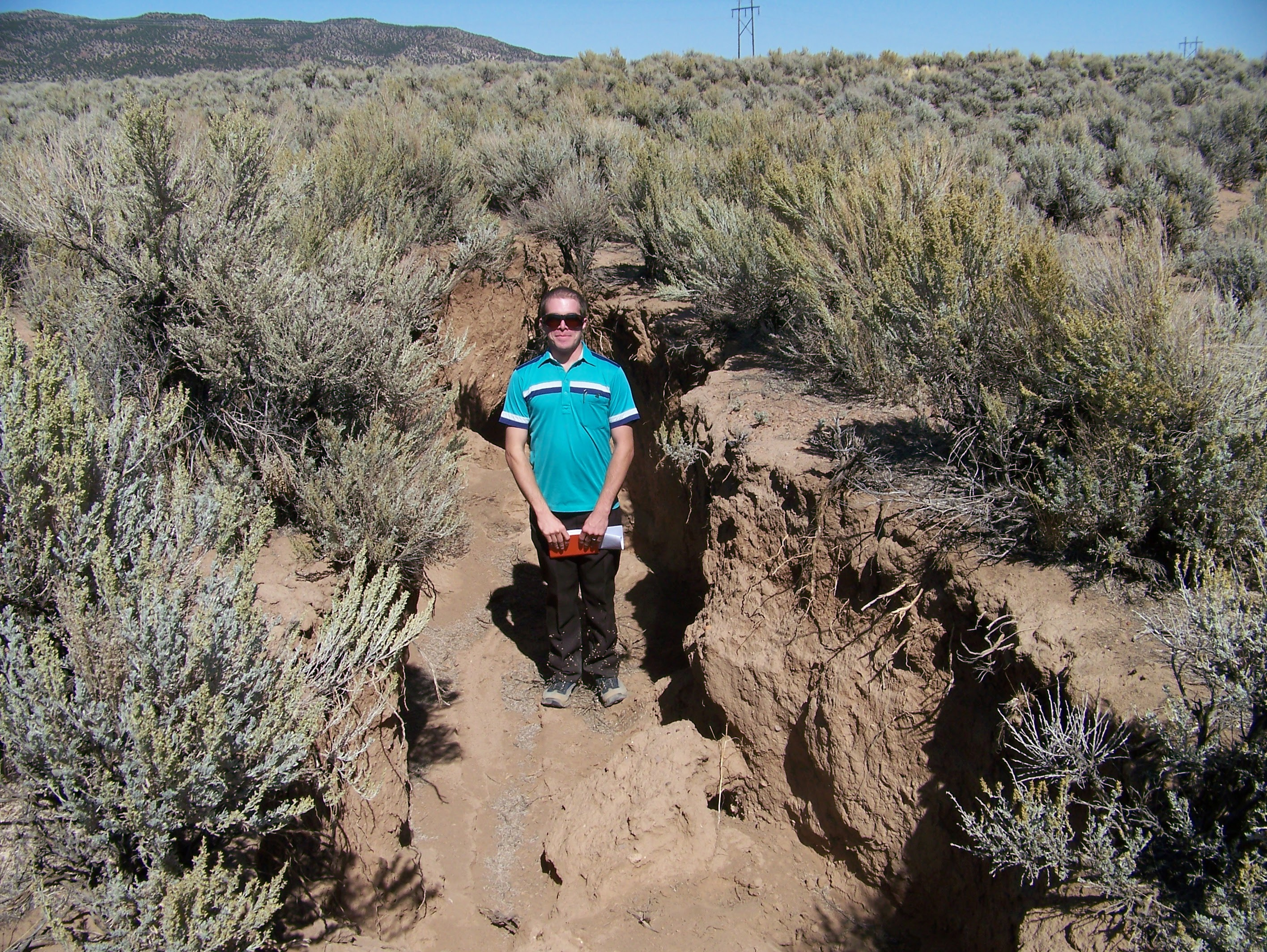 The author stands in a large ditch-like