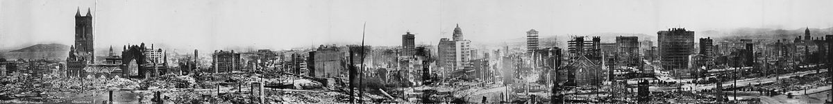 Wide view of rubble and skeletons of buildings that remain, some still smoking.