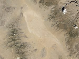 Satellite image of desert dry lake or playa surrounded by mountains.