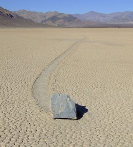 A large rock has slid over the playa surface leaving a track in the mud.
