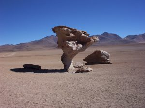 Large rock standing on a narrow base sandblasted by saltating sand blowing near the ground.