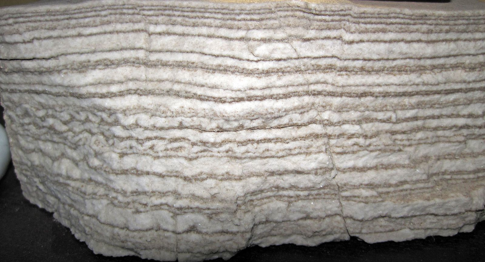 The rock has many light-colored layers.