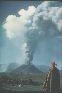 A person looks at the eruption of ash