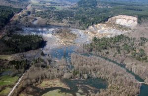 Photo of large slide debris, flood from dammed river, distinct head scarp.