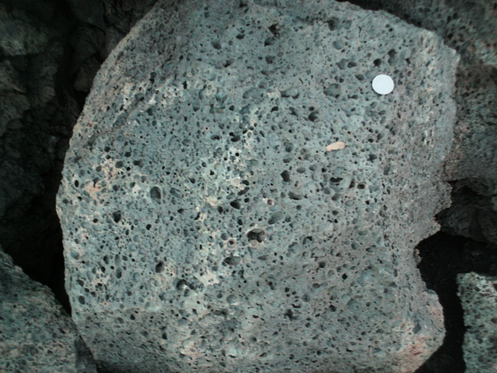 Dark grey rock with many visible holes and no visible crystals.