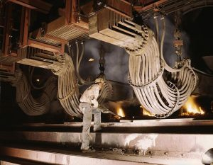 A man is operating a large machine that looks like a blast furnace.