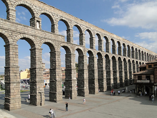 Tall ancient pillars with arched entrances supporting a canal that piped water from the mountains to Roman cities.