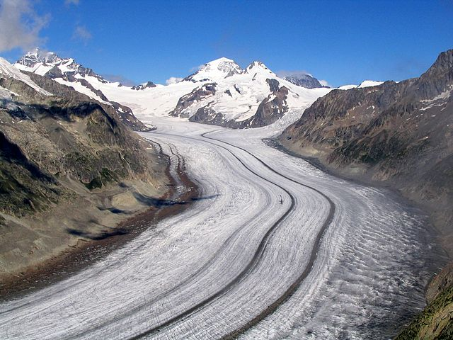 Glacier in the Bernese Alps. A thick sheet of ice filling an alpine valley with lines of sediment (medial moraine).