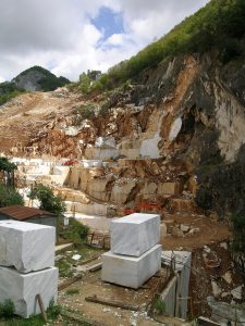 The image shows a hillside with blocks of marble removed.