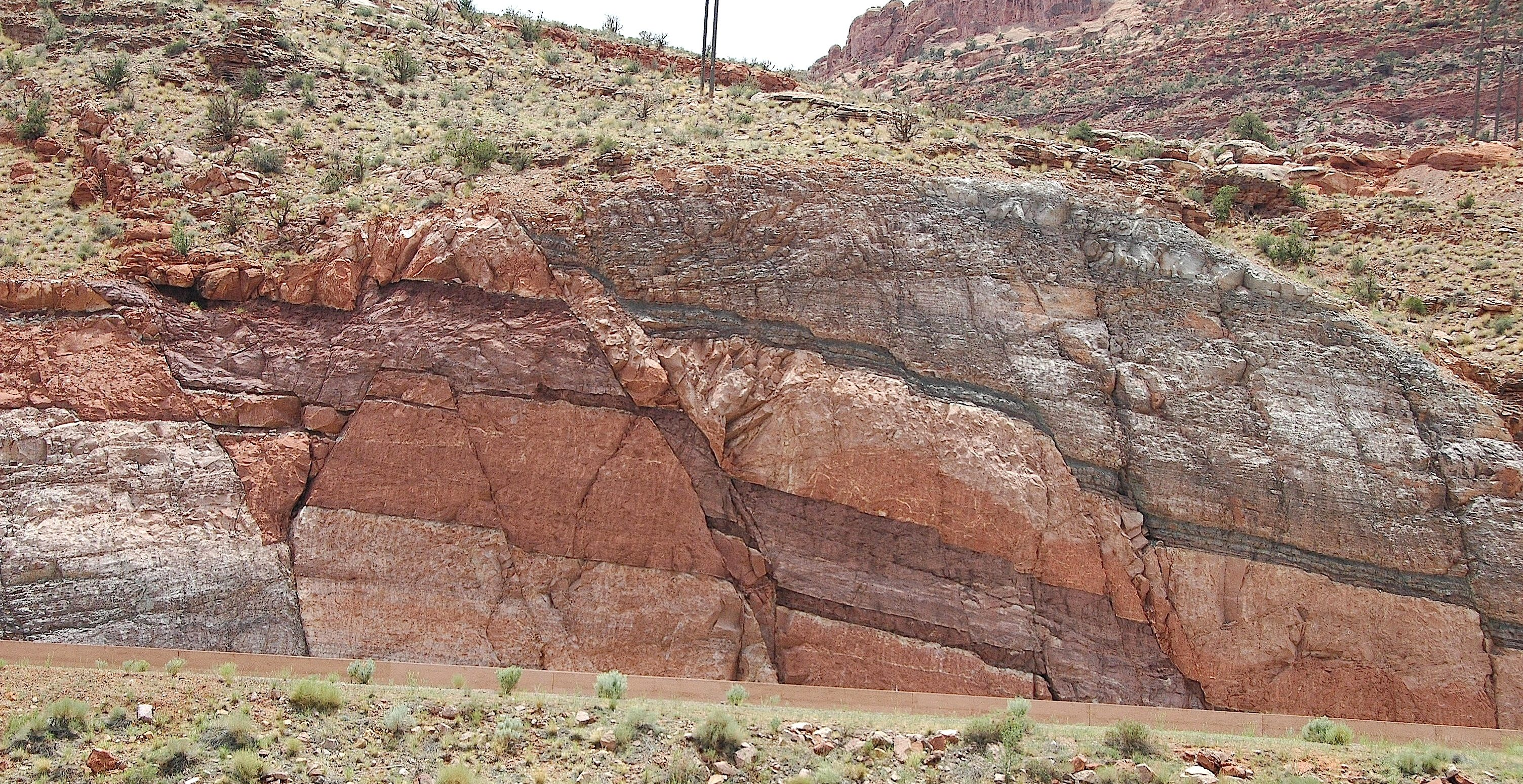 Roadcut outcrop of multicolor rock beds offset by a normal fault.