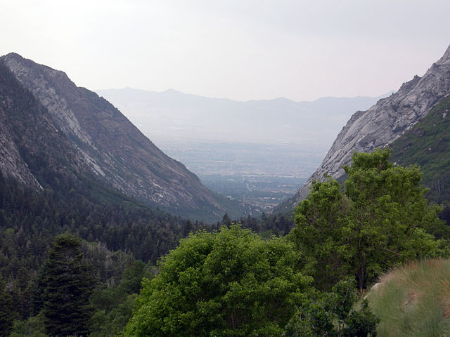 A valley with a u shape that shows steep cliffs on the sides and a wide-flat bottom