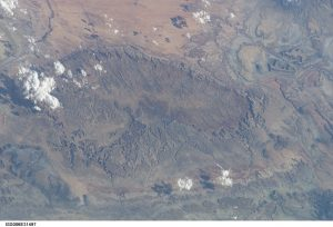 View of a dome in Utah from space. The photo shows upwarped beds of rock, where the center of the dome has been eroded away.