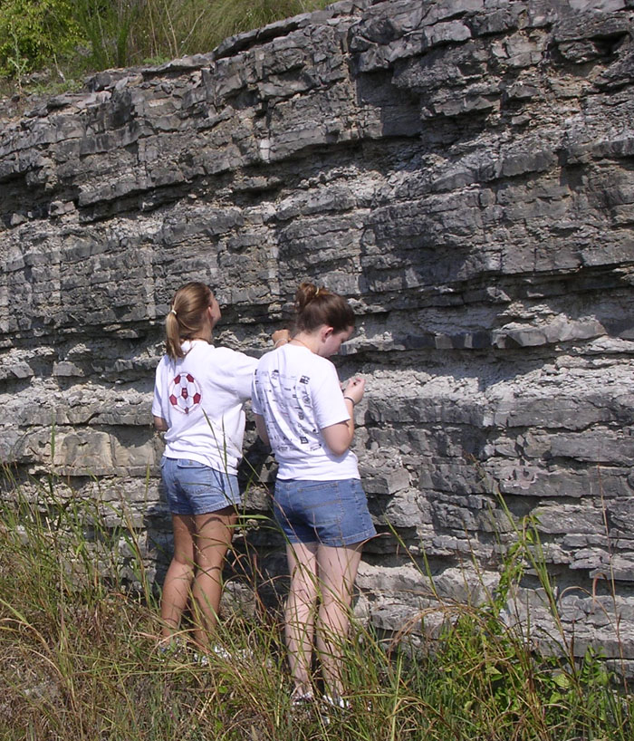Two students are looking at the layers of rock.