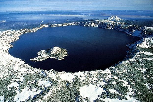 The mountain has a large hole in the center that is filled with the lake.