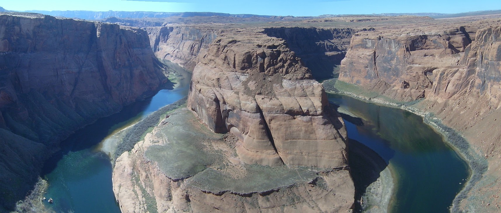 Entrenched meander of the Colorado River, downstream of Page, Arizona. High cliffs, that lead down to a river with narrow shores.