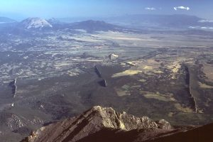 Image shows a mountain top view of a valley with three vertical planes of rock (dikes) jutting out of the surface.